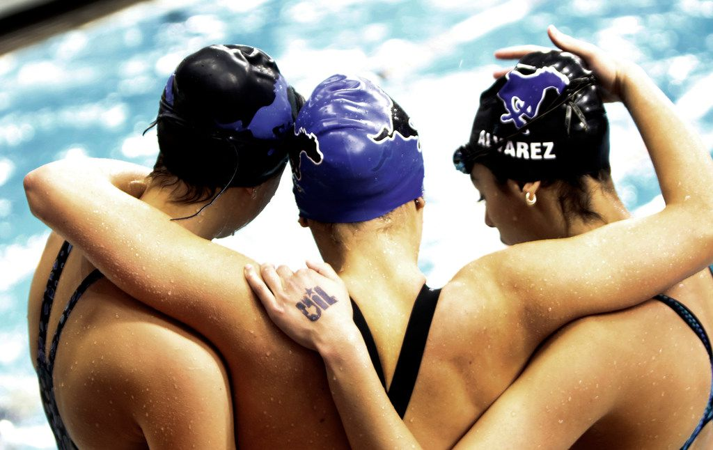 A trio of athletes hug following a swimming event. The UIL Class 6A state swimming and diving finals were held at the University of Texas' Lee and Joe Jamail Texas Swimming Center in Austin on February 15, 2020. (Steve Hamm/Special Contributor).