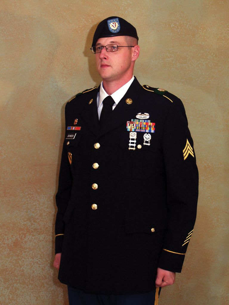 Kevin Bowden stands at attention in uniform during his service in the National Guard.