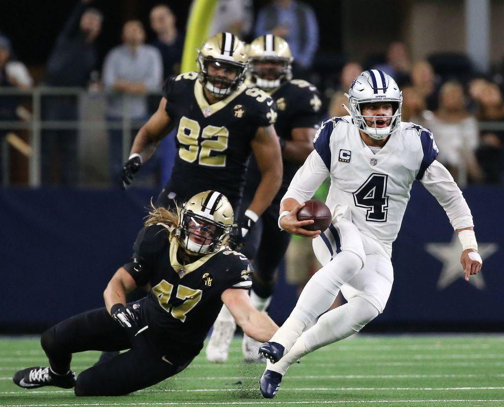 Dallas Cowboys quarterback Dak Prescott (4) runs the ball against New Orleans Saints middle linebacker Alex Anzalone (47) in the second period at AT&T Stadium in Arlington, Texas on Thursday, Nov. 29, 2018. (Rose Baca/The Dallas Morning News)