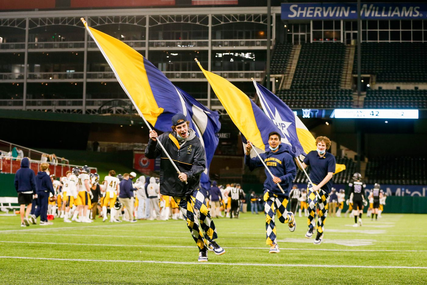 Highland Park flag runners run the field after a touchdown in the fourth quarter of a Class 5A Division I area-round playoff game against Frisco Independence at Globe Life Park in Arlington on Thursday, Dec. 17, 2020. Highland Park won 42-20. (Juan Figueroa/ The Dallas Morning News)