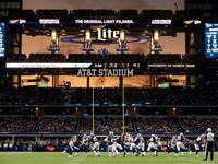 The sunset is seen through the open end zone doors at AT&T Stadium as the Dallas Cowboys ran a second half play against the Los Angeles Rams in Arlington, Texas, Sunday, December 15, 2019. The Cowboys defeated the Rams, 44-21. (Tom Fox/The Dallas Morning News)
