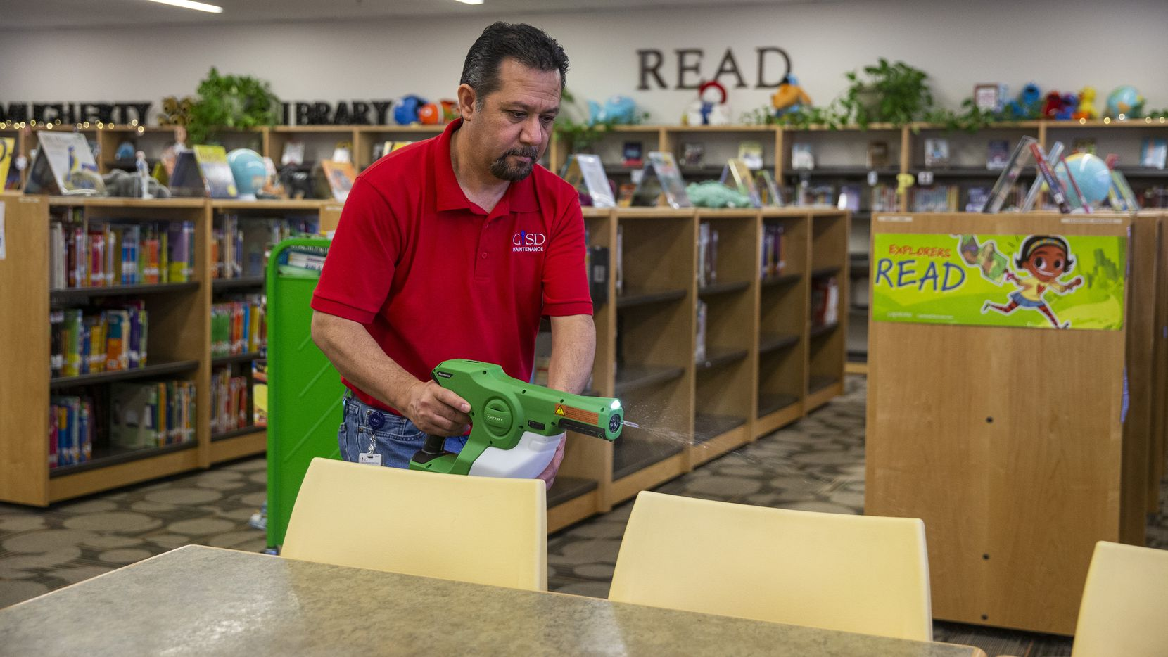 Raúl Rodríguez uses an electrostatic mist in the library at Garland ISD's Daugherty Elementary School to disinfect it of any harmful pathogens and viruses in Garland, Texas, on Wednesday, Jan. 15, 2020. A similar strategy will be applied at campuses if the novel coronavirus reaches schools.