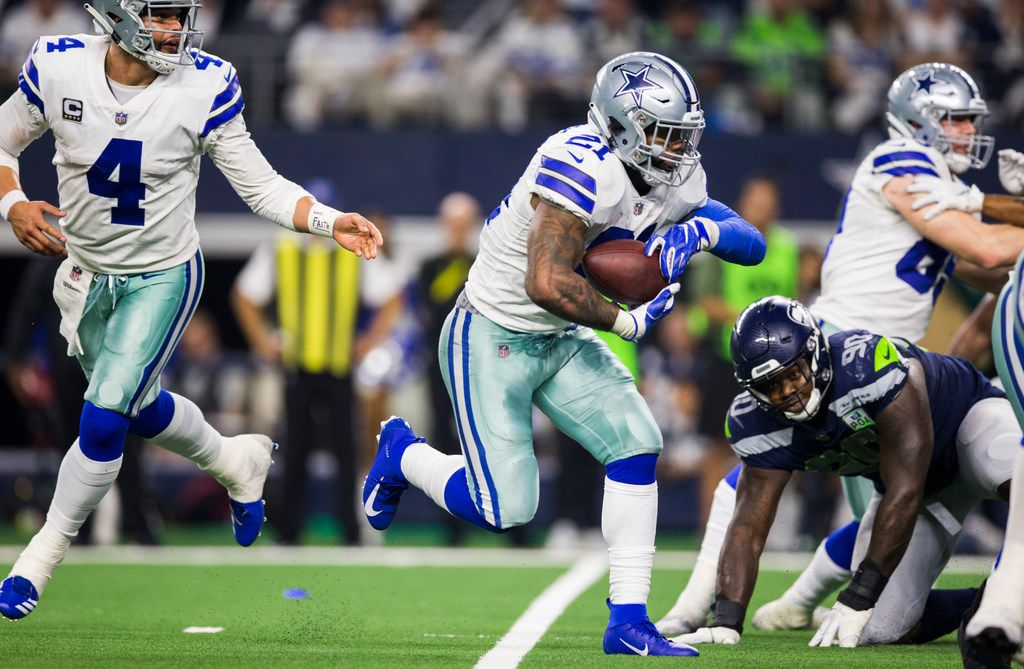 Dallas Cowboys running back Ezekiel Elliott (21) runs to the end zone for a touchdown after a handoff from quarterback Dak Prescott (4) during the fourth quarter of an NFL playoff game between the Dallas Cowboys and the Seattle Seahawks on Saturday, January 5, 2019 at AT&T Stadium in Arlington, Texas. (Ashley Landis/The Dallas Morning News)