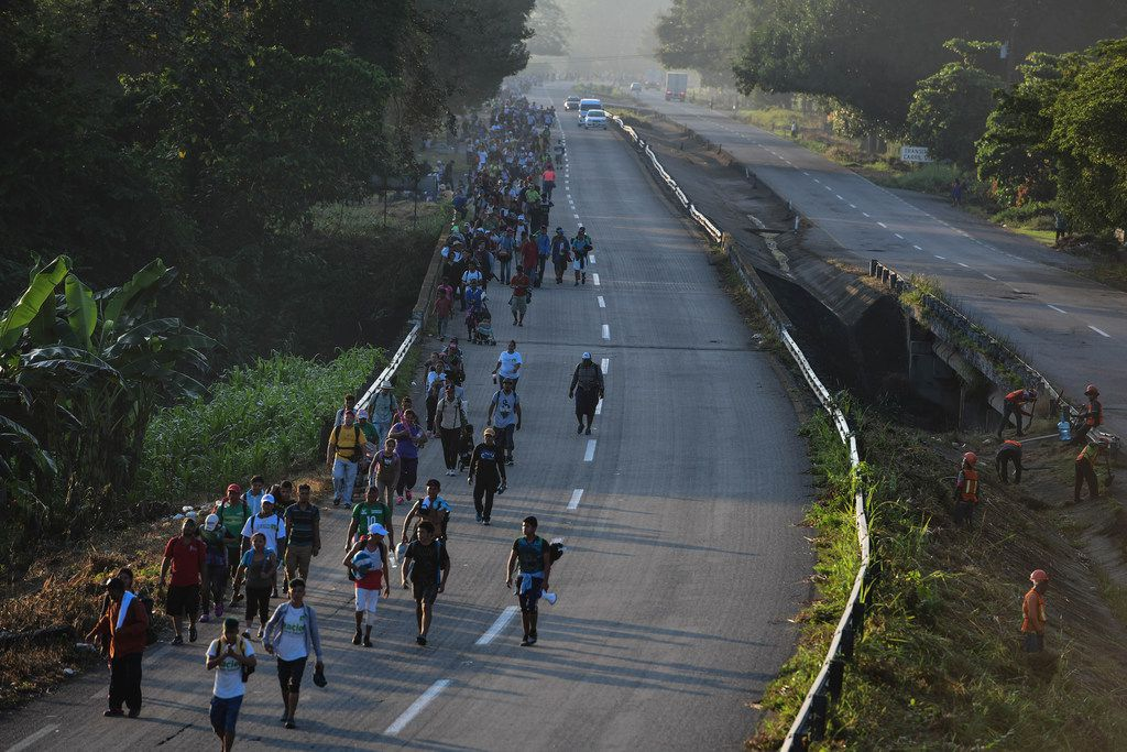 """Thousands of Central American migrants continue their journey toward the U.S. border Wednesday, Oct. 24, 2018, reaching the Mexican coastal town of Mapastepec. An estimated 7,200 migrants from Honduras and other countries have pressed on, sleeping on roads, traveling on rafts, going without food and water and facing police and threats from President Trump, who called them a """"threat"""" and vowed to send troops to the border. (Miguel Juarez Lugo/Zuma Press/TNS)"""
