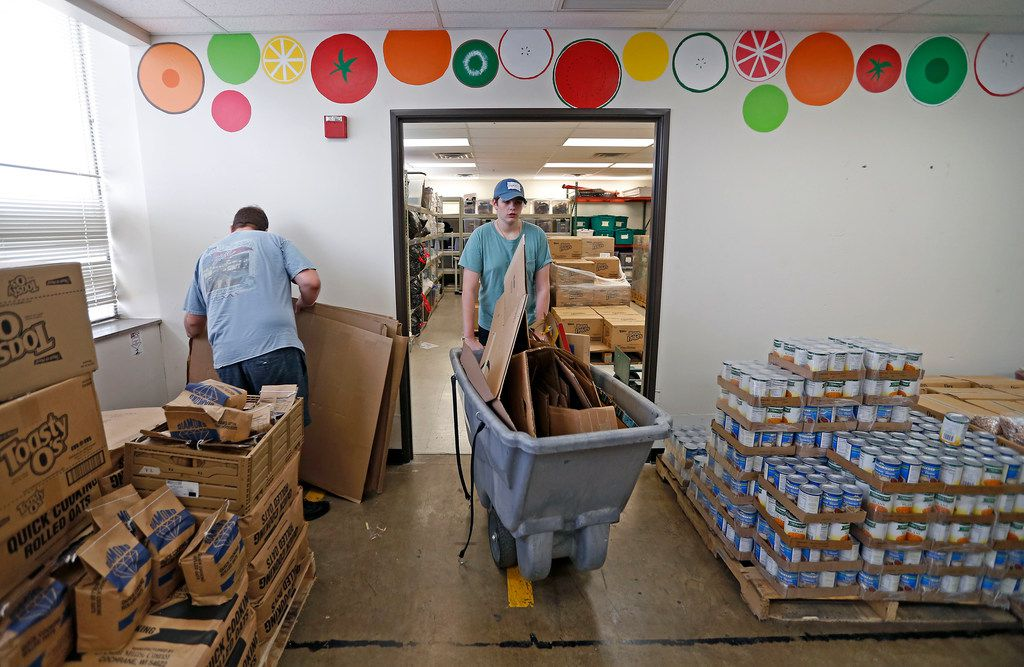 Volunteers Scott Bryan (left), a youth pastor at Tyler Street United Methodist Church, and Reece Hudgins, 17, move empty boxes at Crossroads Community Services.