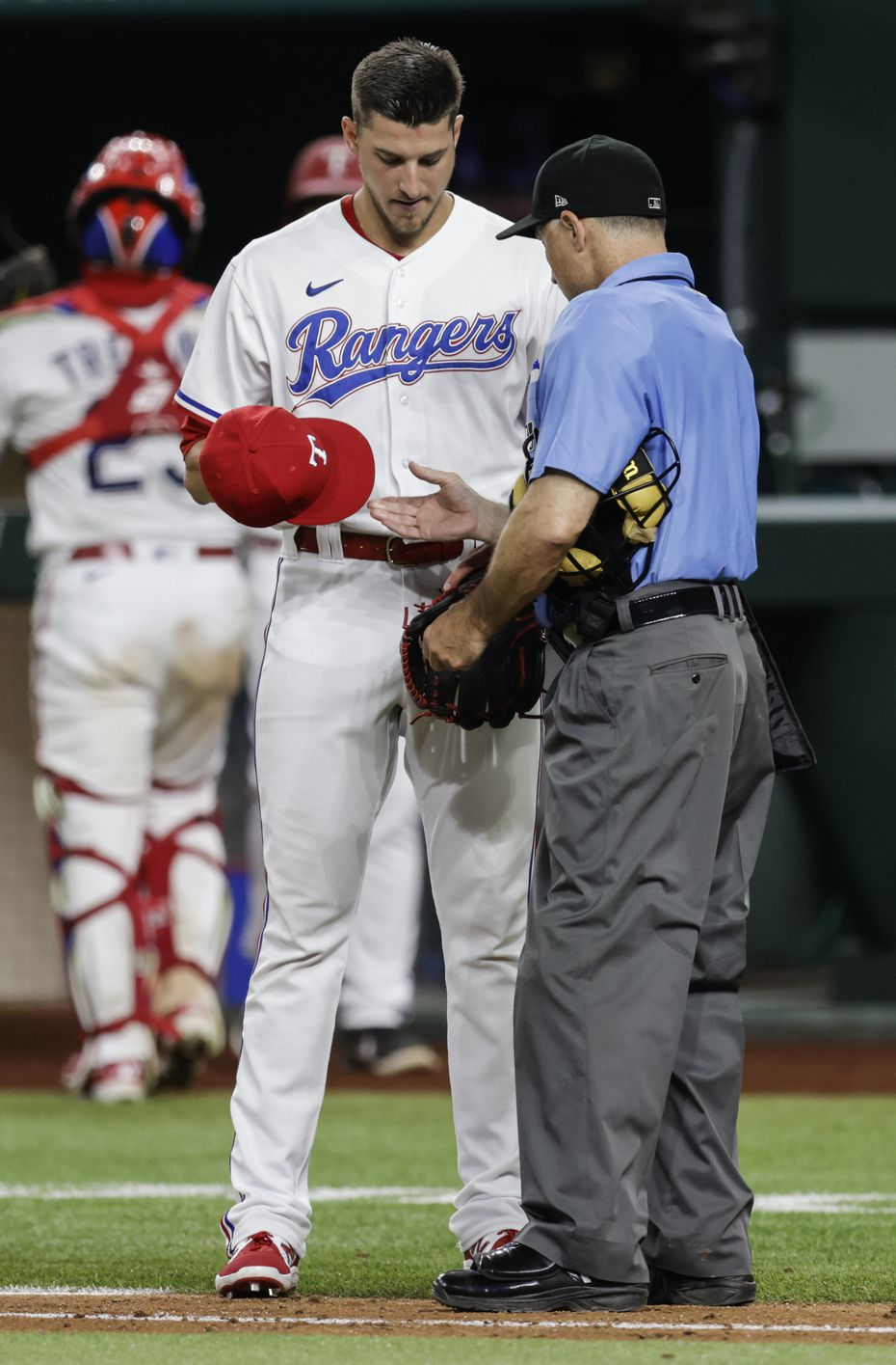 Home plate umpire Dan Iassogna inspects Texas Rangers relief pitcher Brett Martin's (59) glove and hat during the seventh inning of a baseball game against the Oakland Athletics in Arlington, Monday, June 21, 2021.