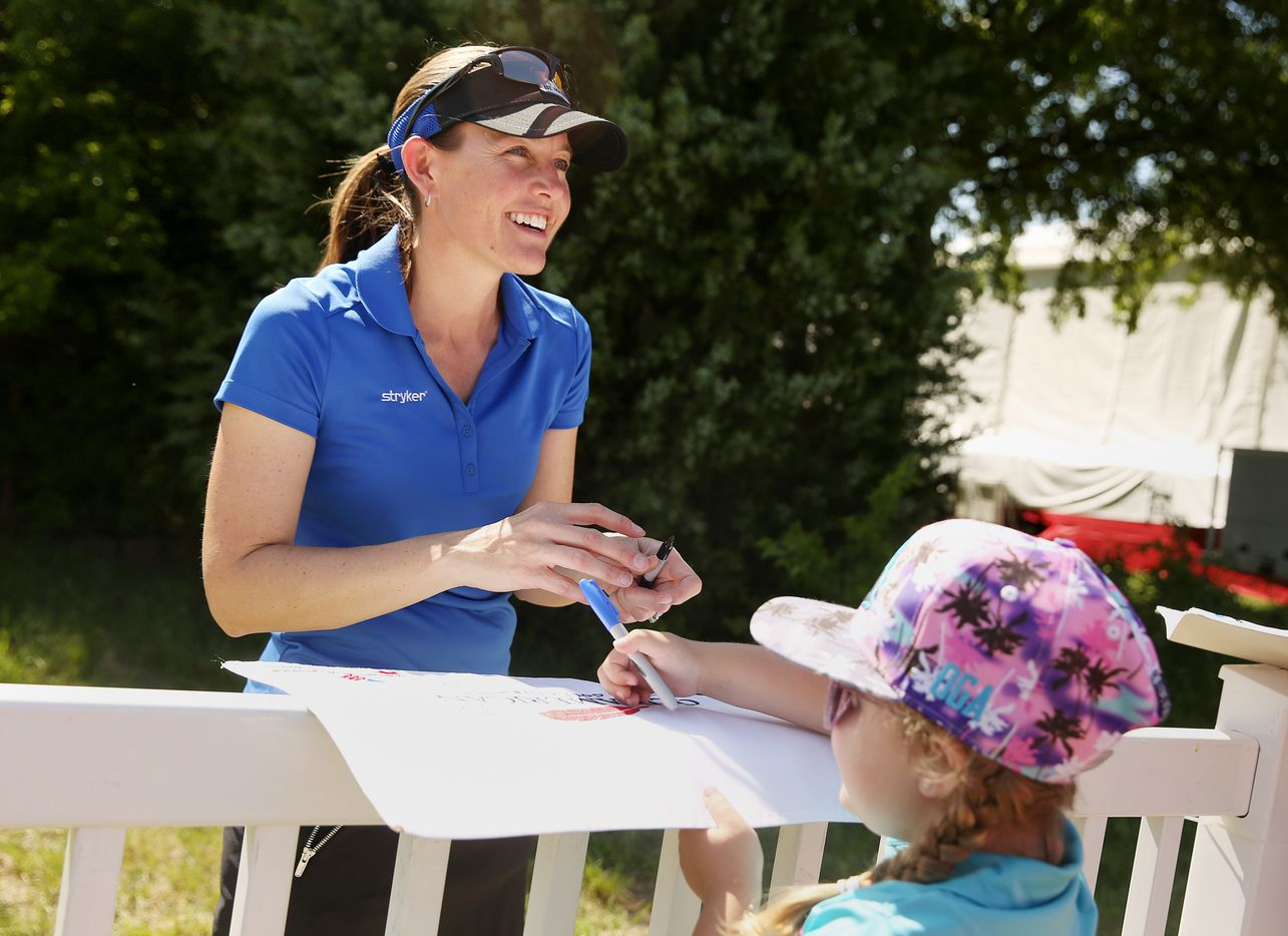 Stephanie Louden, of Frisco, Texas, signs an autograph for a young fan after round one of the 36-hole revised Volunteers of America LPGA North Dallas Classic at the Old American Golf Club.