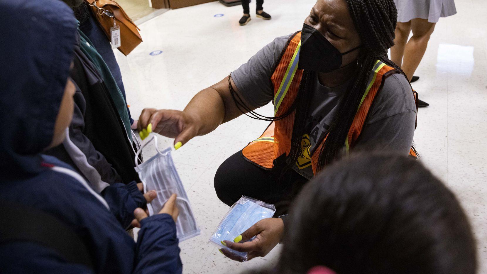 Shanieka Christmas-McDonald, directora de la primaria H.I. Holland,  entrega mascarillas a estudiantes durante la primera semana de clases. Miles de estudiantes se ausentaron en las primeras semanas en el DISD.