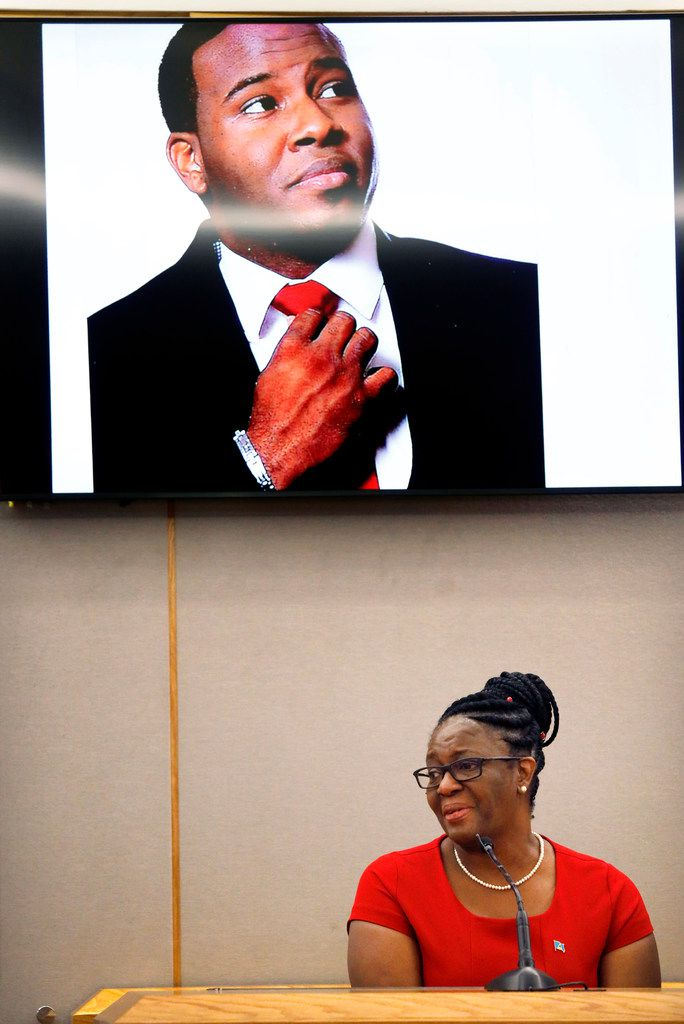 Botham Jean's mother, Allison Jean, speaks to the jury about her son during the sentencing phase of the trial in October as his image fills the screen above her.
