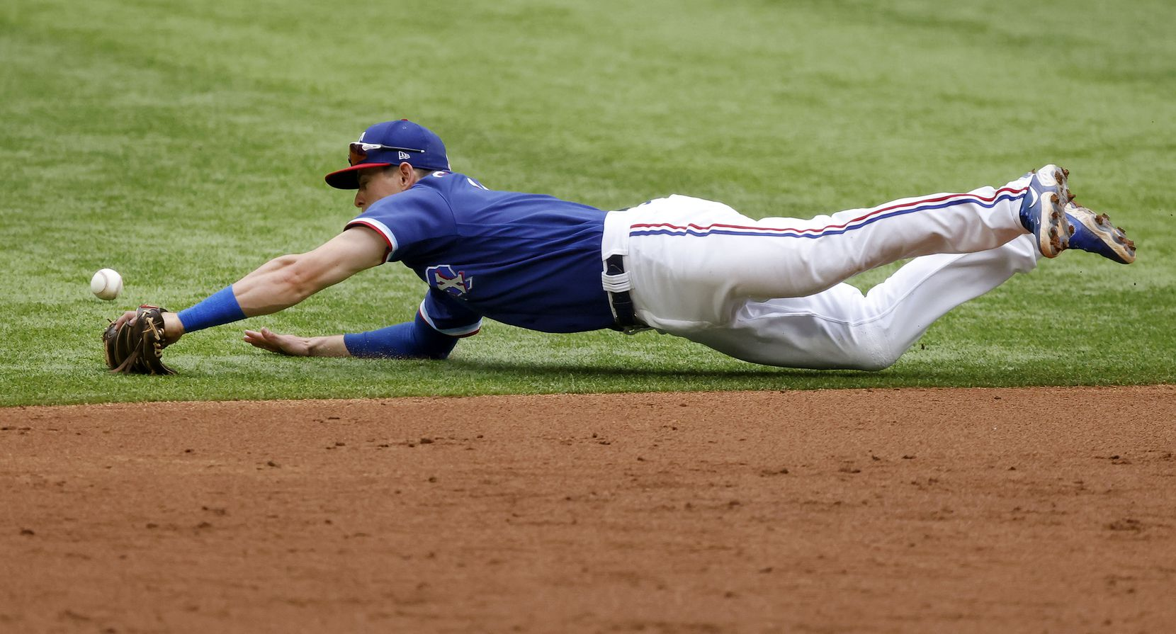 Texas Rangers second baseman Nick Solak (15) dives and narrowly misses a grounder by Milwaukee Brewers batter Lorenzo Cain in the third inning at Globe Life Field in Arlington, Texas. The teams were playing in an exhibition game, Tuesday, March 30, 2021. (Tom Fox/The Dallas Morning News)12