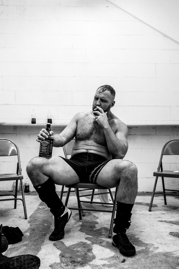 Jon Moxley smokes a cigarette while holding a bottle of Jack Daniels following his match at Game Changer Wrestling's Bloodsport on October 11, 2020. The portrait appears in the new, glossy art magazine about wrestling culture, Orange Crush, a passion project edited by art adviser and fan Adam Abdalla.