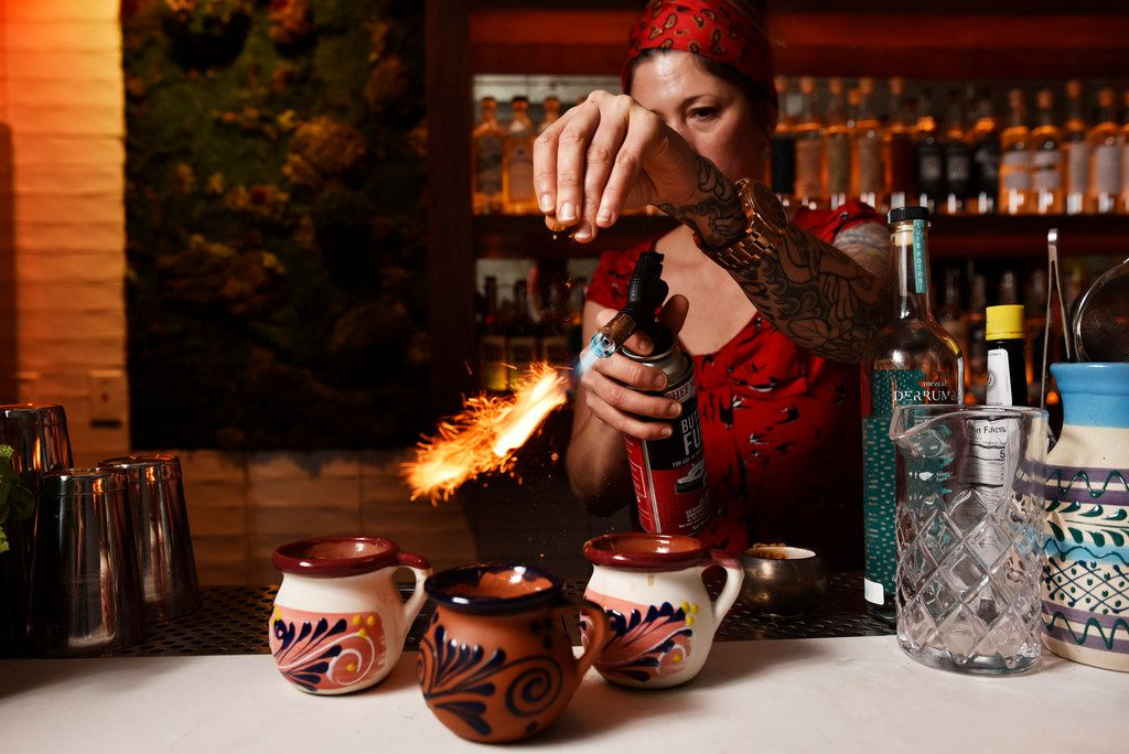 La Viuda Negra bar manager Candice Ruibal uses a blowtorch to toast cinnamon as she sprinkles it over cups of curado de pulque, a Mexican alcoholic drink made from fermented maguey sap.