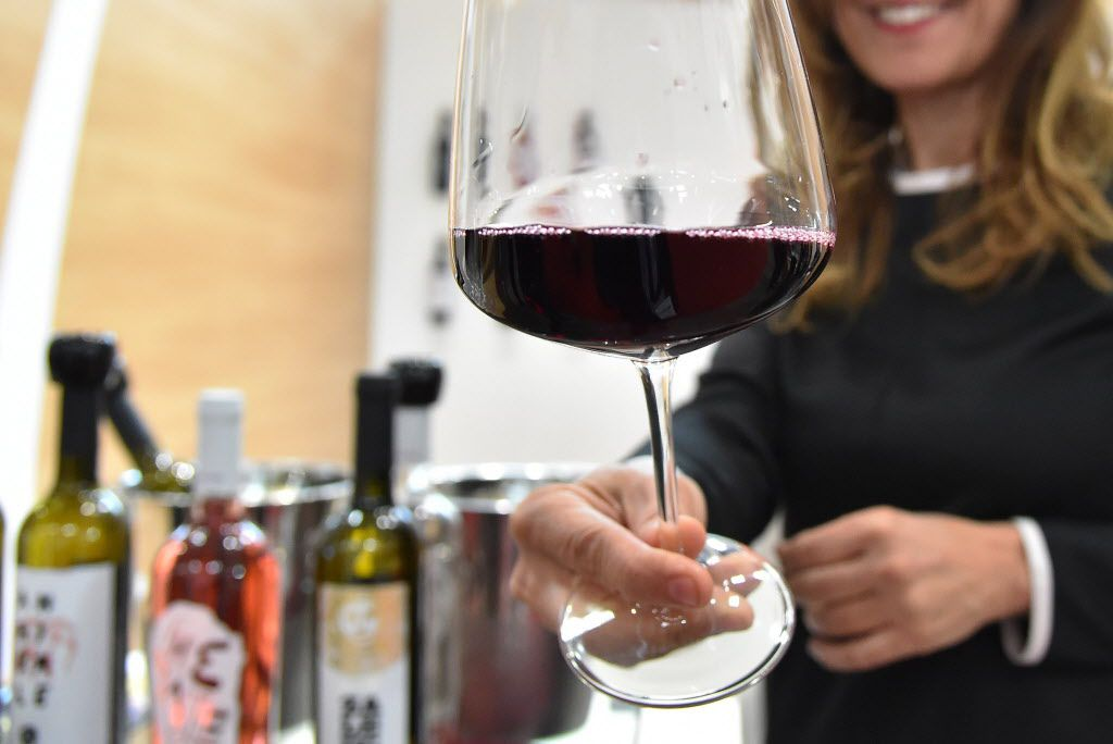 """A woman hands a glass of wine from the """"Le Moire"""" wine maker of the Italian Calabria region on April 10, 2016 during the 50th edition of the Vinitaly wine exhibition in Verona."""