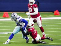 Dallas Cowboys running back Ezekiel Elliott (21) fumbles on a hit from Arizona Cardinals strong safety Budda Baker (32) during the first quarter of an NFL football game at AT&T Stadium on Monday, Oct. 19, 2020, in Arlington. The Cardinals recovered the fumble.