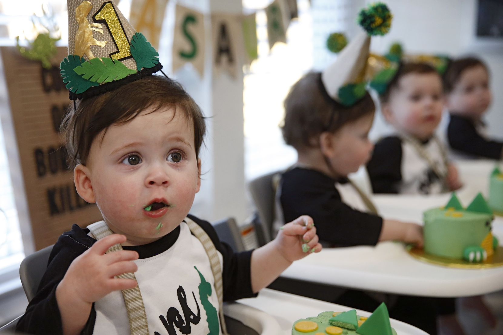 Harrison Marr reacts as he tastes icing on the cake along with his brothers Hardy, Henry, and Hudson Marr during their one-year birthday party at their home on Monday, March 15, 2021, in Grapevine, Texas.
