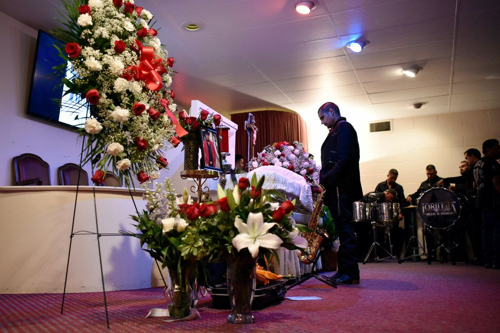 A bandmate from the music group Lobillos Musical de Durango pauses in front of the casket of Raul Ortega Cabrera, who was killed Monday when a building under construction in West Dallas collapsed in a storm.