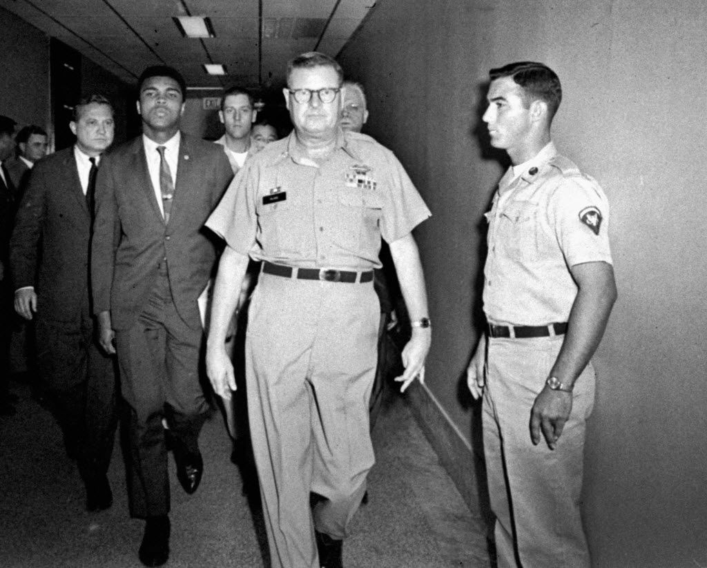 ADVANCE FOR USE SUNDAY, FEB. 23, 2014 AND THEREAFTER - FILE - In this April 28, 1967 file photo, heavyweight boxing champion Muhammad Ali is escorted from the Armed Forces Examining and Entrance Station in Houston by Lt. Col. J. Edwin McKee, commandant of the station, after Ali refused Army induction. Ali says he was a conscientious objector who would not serve in the Army of a country that treated members of his race as second-class citizens. (AP Photo)
