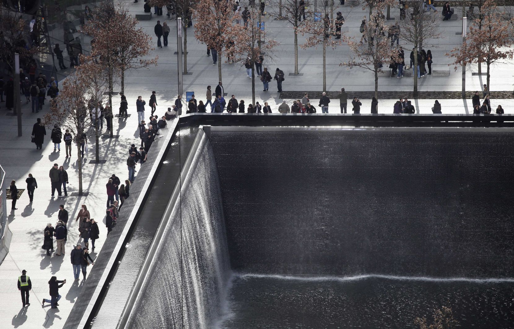Visitors to the National September 11 Memorial and Museum circle one of two reflecting pools, on Nov. 21, 2011, in New York.