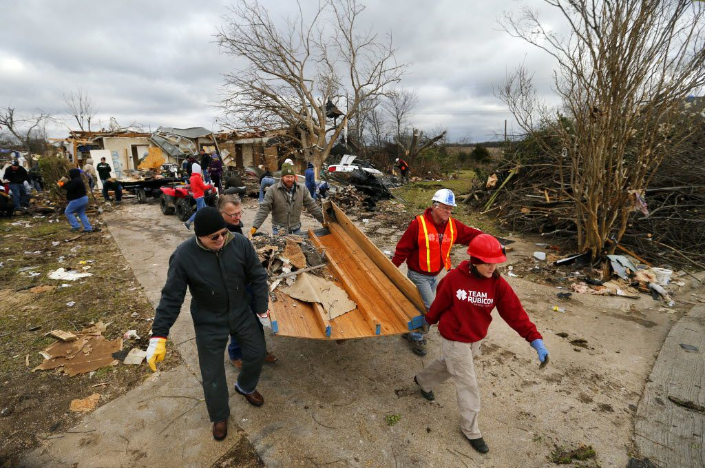 A volunteer group from West Texas District Church of the Nazarene, led by Team Rubicon, carried debris from a destroyed home while cleaning up a tornado-ravaged neighborhood in Glenn Heights in early January 2016.
