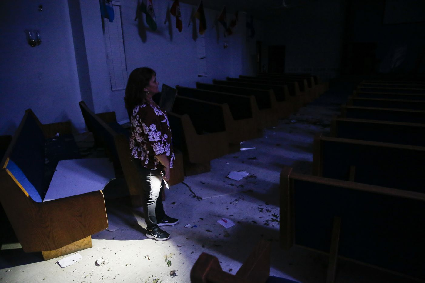 Elvira Rodriguez views damage left behind at Primera Iglesia Dallas church by a Sunday night tornado is seen at the church just off of Walnut Hill Lane in Dallas, on Monday, Oct. 21, 2019. (Ryan Michalesko/The Dallas Morning News)