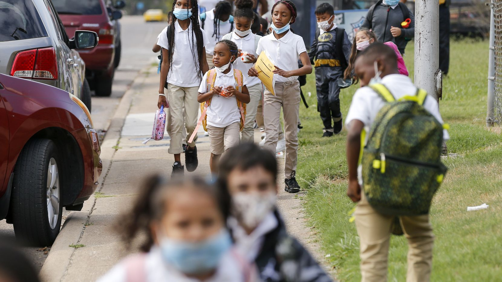 Children walk along a sidewalk after school at Paul L. Dunbar Learning Center in Dallas on Wednesday, Sept. 8, 2021. Dallas ISD is one of the districts that has issued a mask mandate.
