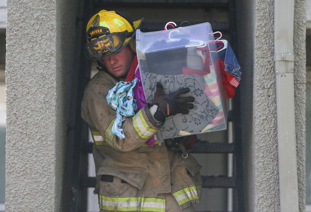 A firefighter salvaged children's clothing from a burned apartment unit.