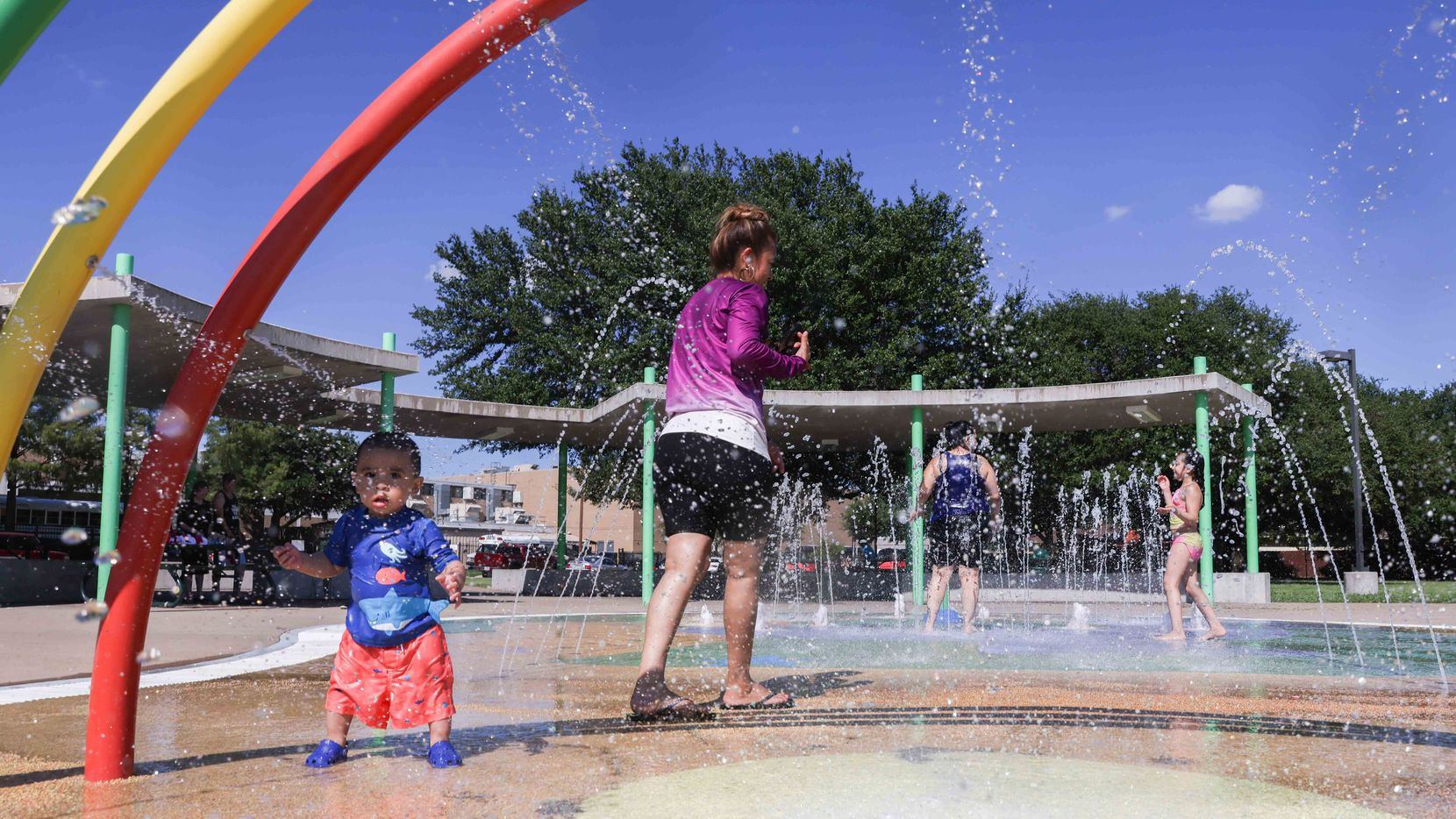 Adults and kids cool off from heat in a splash pad at Fergunson Park while a clear sky over Dallas takes feels like temperatures to the triple digits on Tuesday, August 24, 2021. (Lola Gomez/The Dallas Morning News)