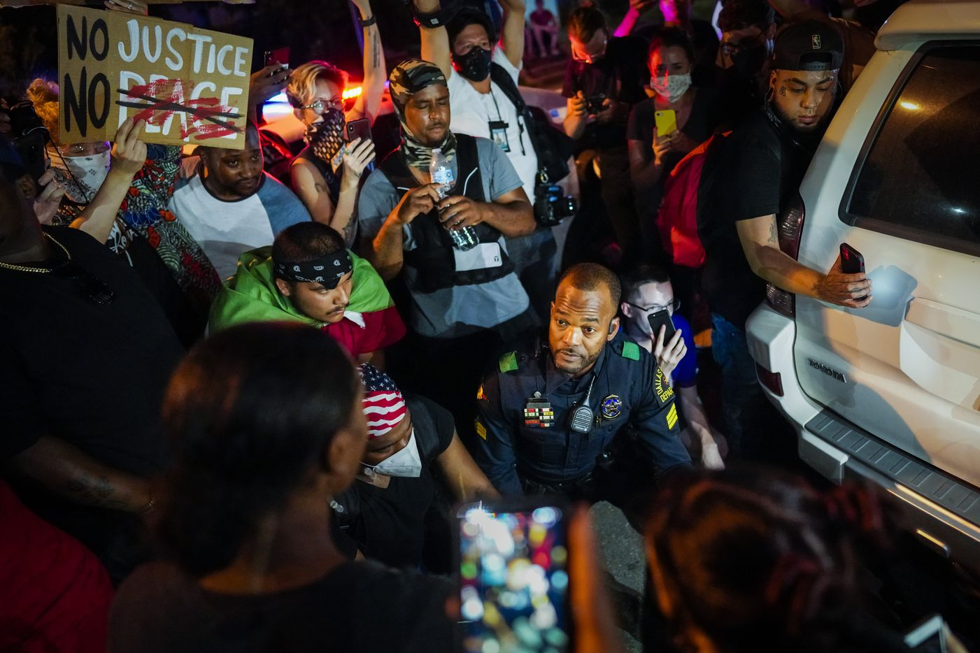 A Dallas police officer stops and gets our of his car to talk and take photos with a group of demonstrators gathered at Lake Cliff Park as protests continue after the death of George Floyd on Tuesday, June 2, 2020, in Dallas. Because of the city imposed 7:00 p.m. curfew, the group moved from Dallas City Hall to outside the curfew zone in Oak Cliff.