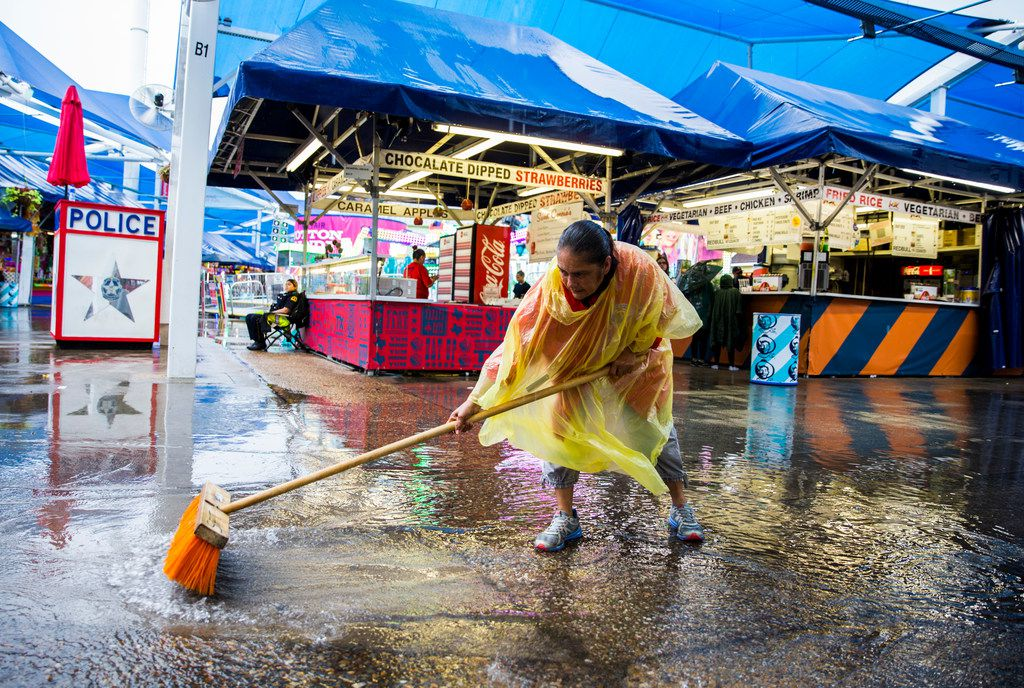 State Fair of Texas employee Mary Muniz uses a broom to move puddles of rain water closer to a drain in the midway on Tuesday, October 9, 2018 at Fair Park in Dallas.