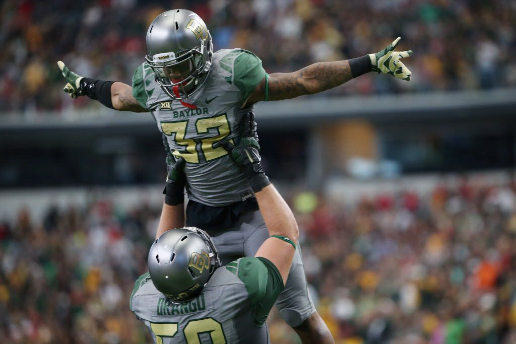 Baylor Bears offensive tackle Spencer Drango (58) lifts Baylor Bears running back Shock Linwood (32) after Linwood scored an 8-yard rushing touchdown in the second quarter during an NCAA football game between Texas Tech and Baylor at AT&T Stadium in Arlington, Texas Saturday October 3, 2015. (Andy Jacobsohn/The Dallas Morning News)
