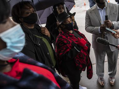 Claudia Fowler, center, speaks during a press conference conducted by a group of Black advocates as they call for action from Dallas Mayor Eric Johnson to help improve the access to the COVID-19 vaccine for people of color, on Thursday, Jan. 21, 2021 outside of Fair Park in Dallas.