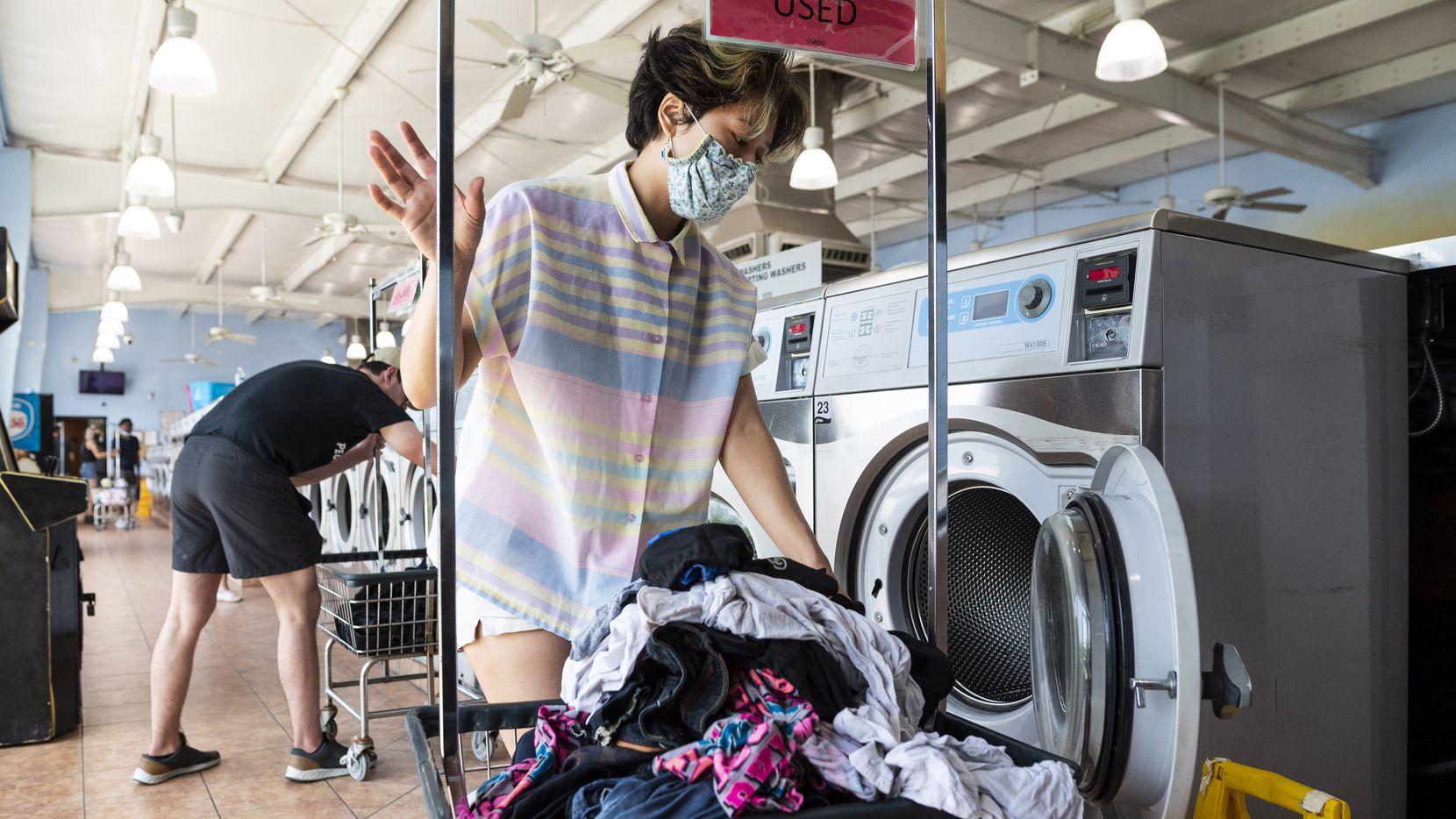 Una voluntaria ayuda a lavar ropa para Say It With Your Chest, una organización que ayuda a personas indigentes lavándoles su ropa en Xpress Wash N Dry en Dallas.