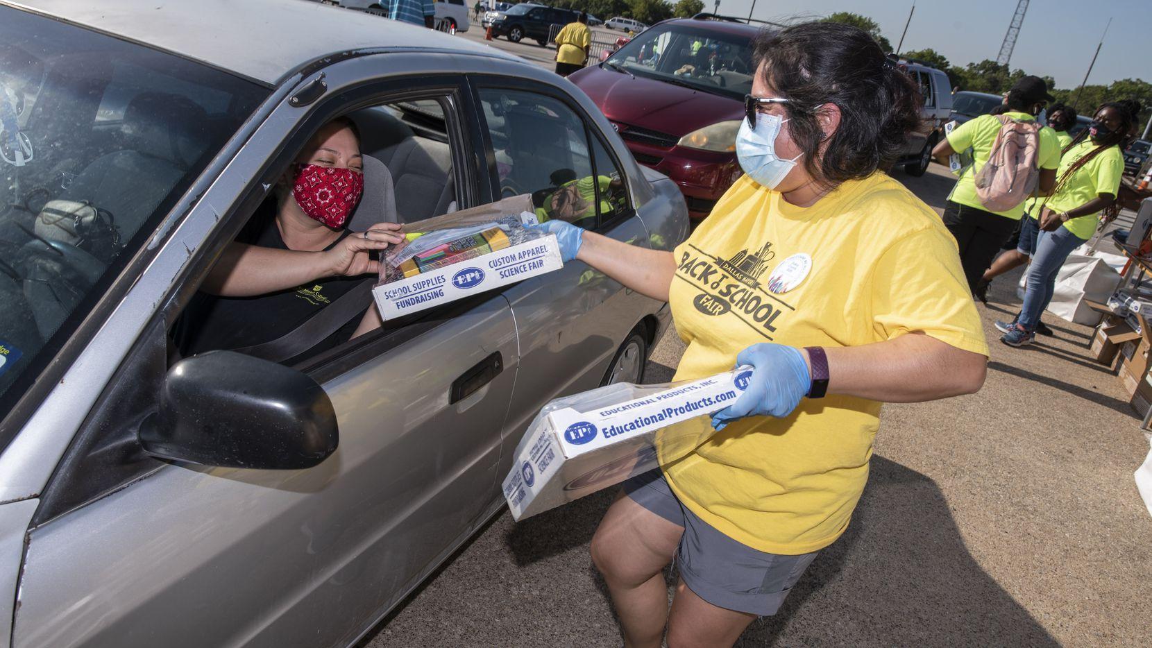 La voluntaria Sandra Cuéllar entrega útliles escolares para familias de Dallas durante la Feria de Regreso a Clases del Alcalde que por segundo año consecutivo se realizará mediante el sistema drive-thru.