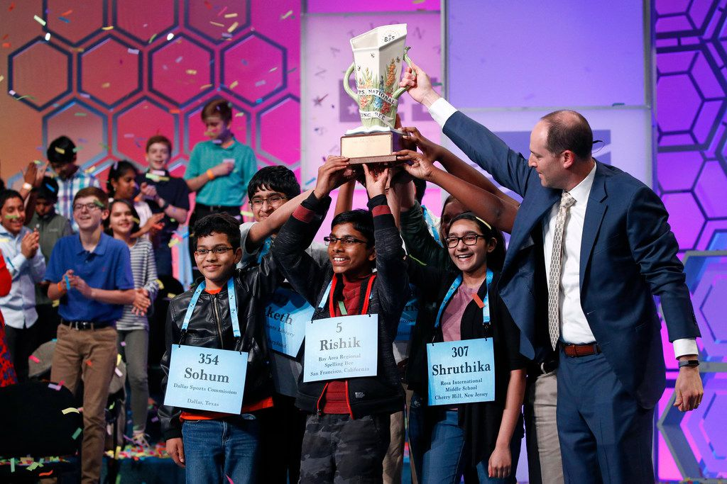 E.W. Scripps CEO Adam Symson, right, presents a trophy to the eight co-champions of the Scripps National Spelling Bee, Friday, May 31, 2019, in Oxon Hill, Md. The spelling bee ended in unprecedented 8-way championship tie after organizers ran out of challenging words.  (AP Photo/Patrick Semansky)