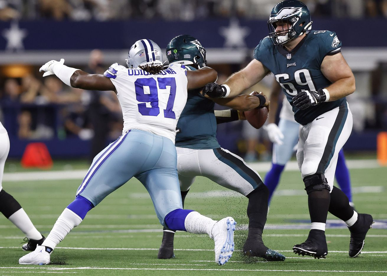 Dallas Cowboys defensive tackle Osa Odighizuwa (97) gets the sack of Philadelphia Eagles quarterback Jalen Hurts (1) after getting around center Landon Dickerson (69) during the second quarter at AT&T Stadium in Arlington, Monday, September 27, 2021. (Tom Fox/The Dallas Morning News)