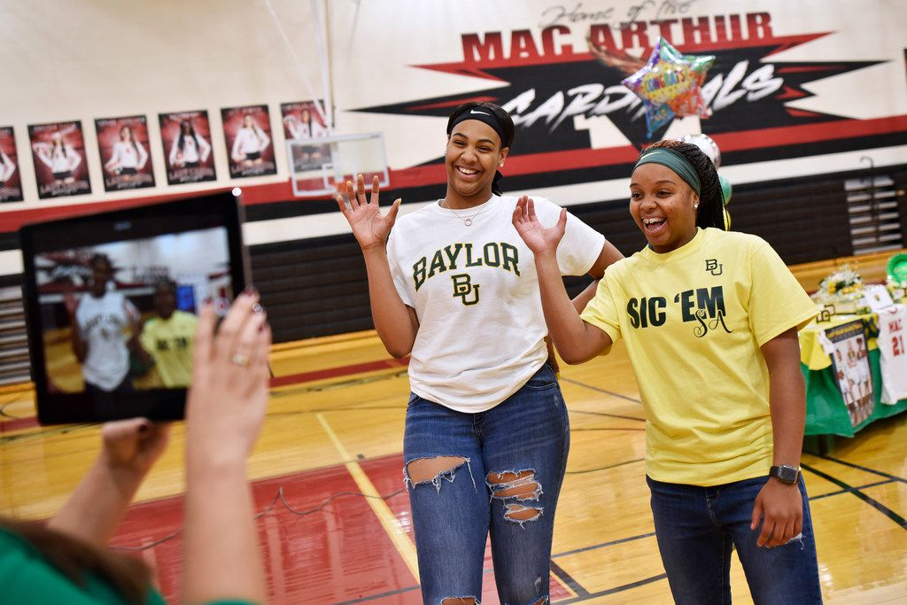 Irving MacArthur girls basketball players Hannah Gusters, left, and Sarah Andrews, make the hand signal for the Baylor Bears while being interviewed for Irving ISD before signing their letters of intent to play for Baylor University, Wednesday night Nov. 13, 2019 at Irving MacArthur High School in Irving. Ben Torres/Special Contributor