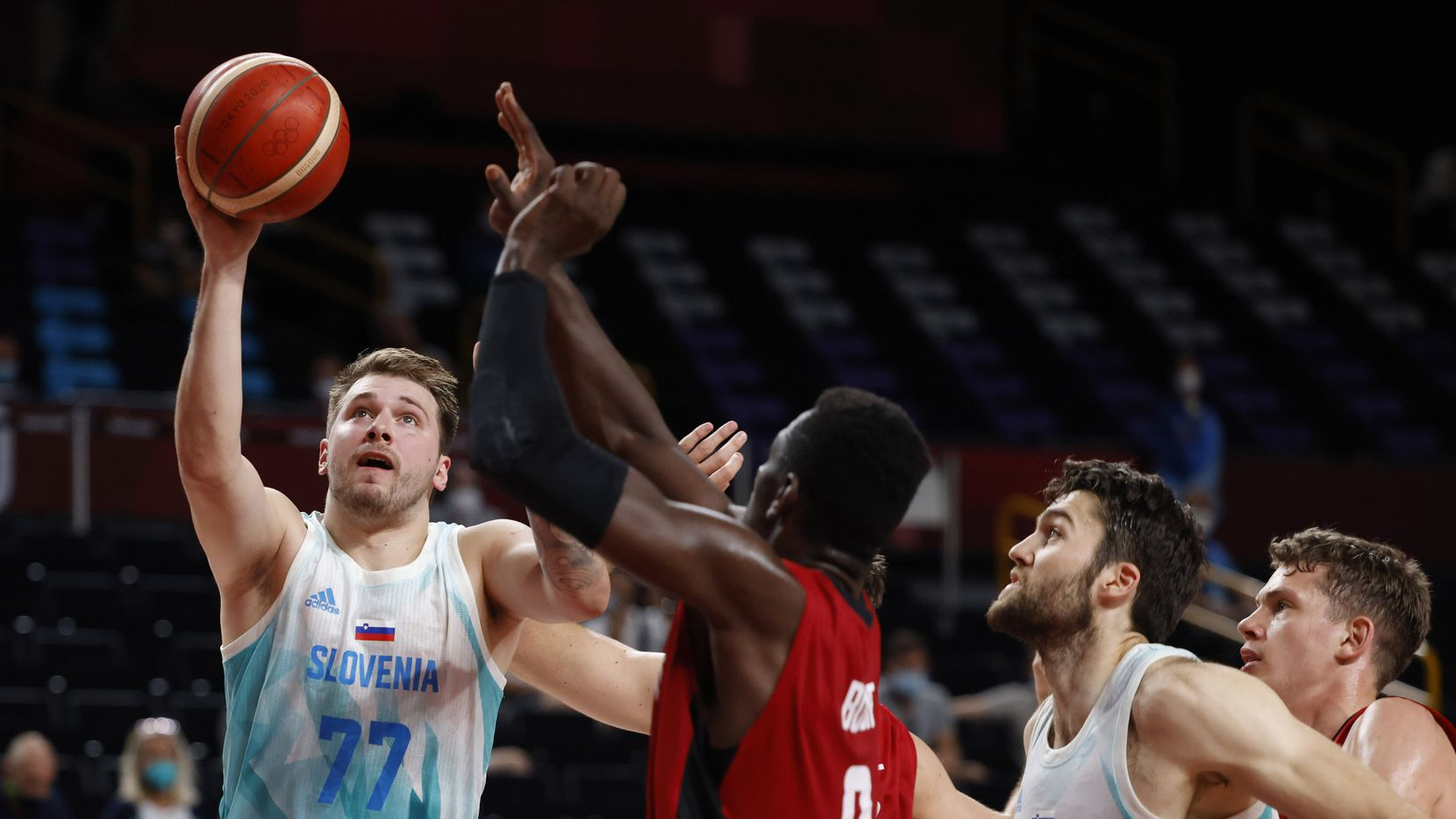 Slovenia's Luka Doncic (77) attempts a shot on Germany's Isaac Bonga (0) during the first half of play of a quarter final basketball game at the postponed 2020 Tokyo Olympics at Saitama Super Arena, on Tuesday, August 3, 2021, in Saitama, Japan. (Vernon Bryant/The Dallas Morning News)