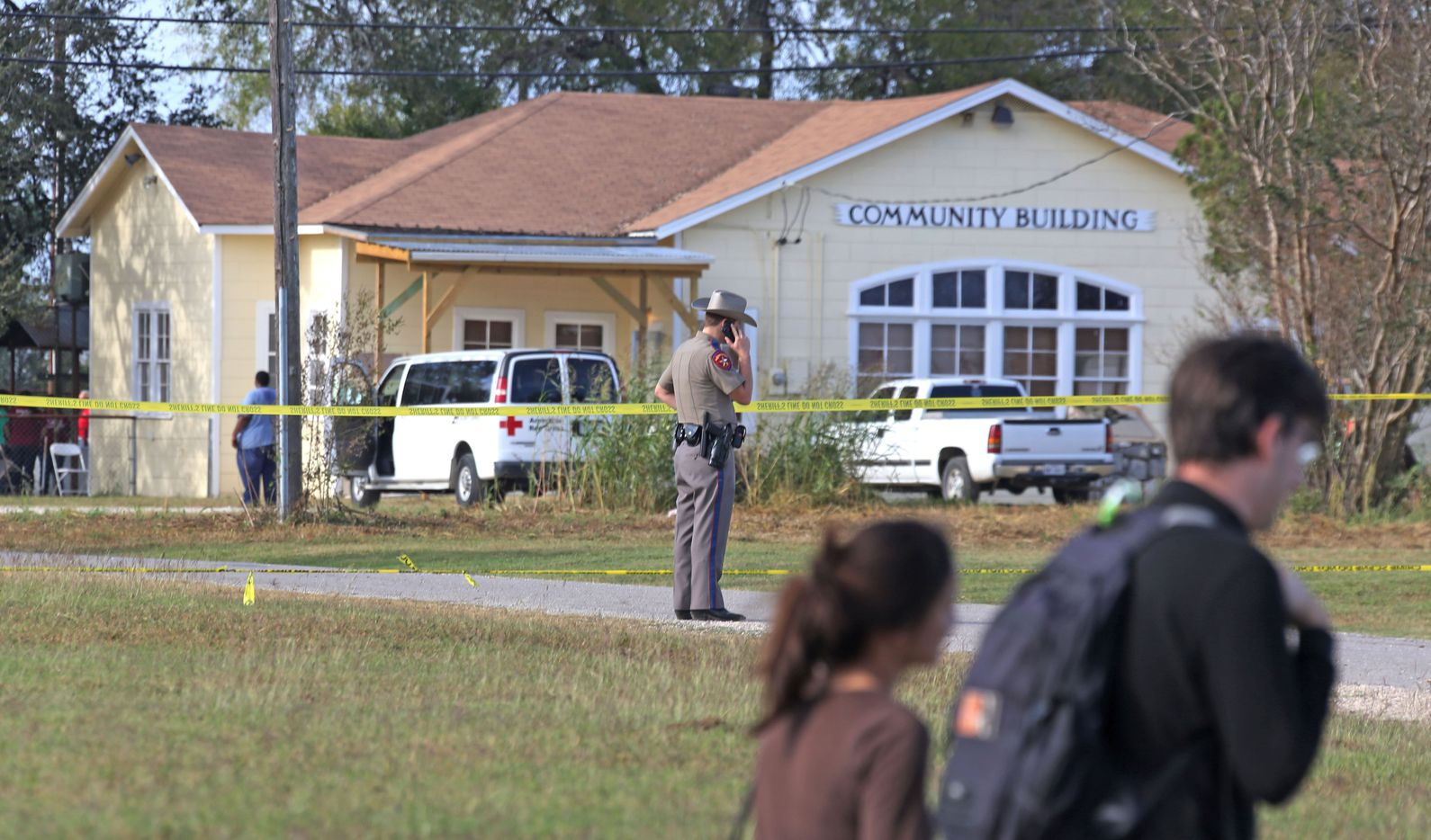 People walk past the community building near the First Baptist Church of Sutherland Springs, Texas. At least 26 people died Sunday after a gunman opened fire at a Baptist church in the small town southeast of San Antonio. Photographed on Monday, November 6, 2017. (Louis DeLuca/The Dallas Morning News)