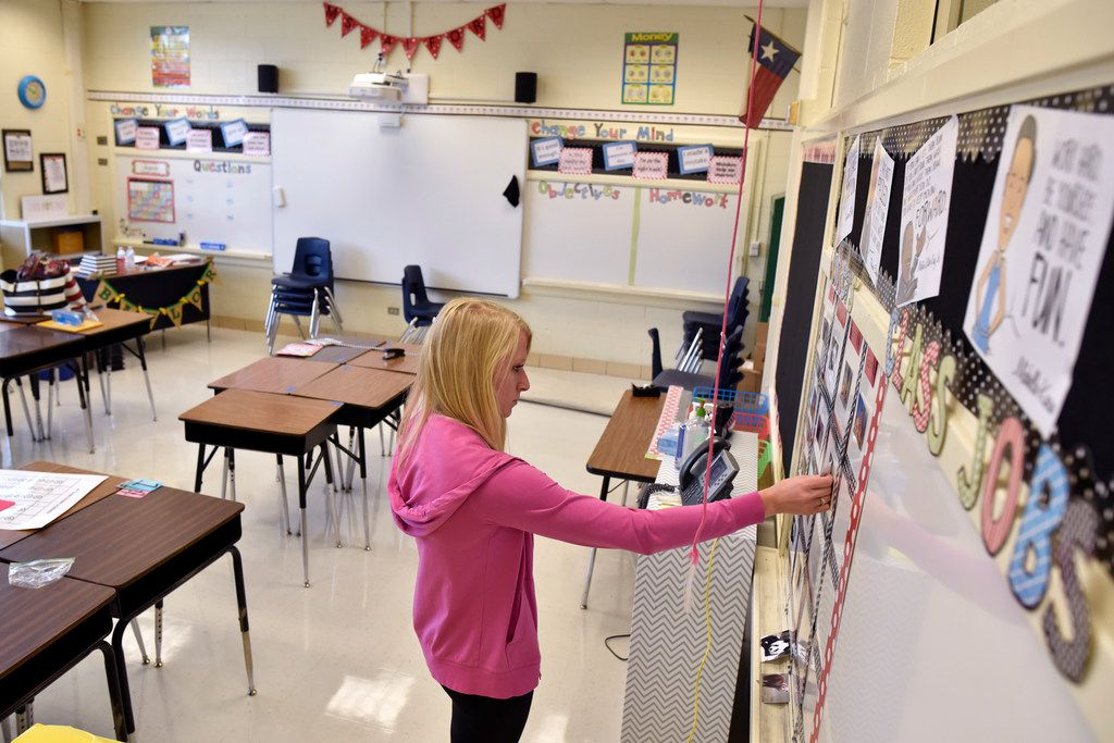 Katherine Alford organizes a education bulletin board as she prepares her fourth-grade math classroom for the first day of school at Terrance Elementary on Thursday in Richardson.
