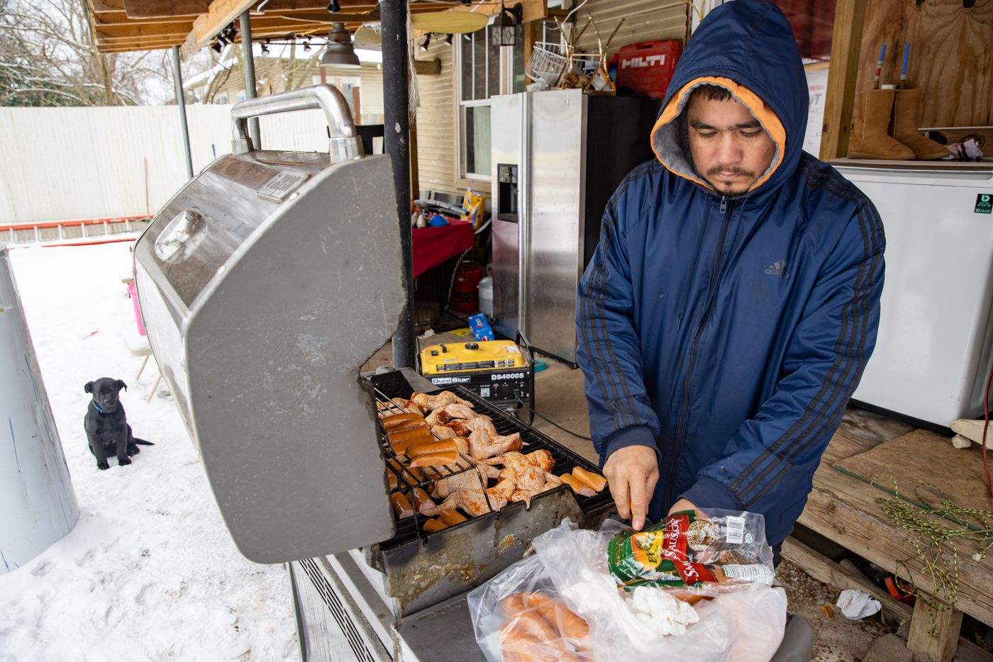 Franco Pompa grills chicken in his backyard at his East Dallas home on Wednesday, Feb. 17, 2021. One of the generators is also being used to power neighbor Leonel Solis' home through a long extension cord.