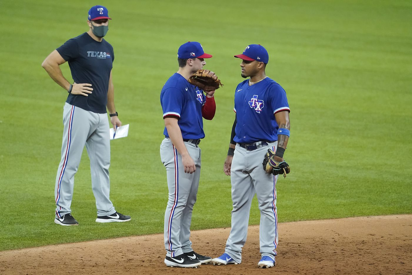 Texas Rangers infielder Justin Foscue (center) talks with infielder Andy Ibanez as field coordinator Matt Hagen looks on during a game between players at the team's alternate training site at Globe Life Field on Saturday, Sept. 19, 2020.