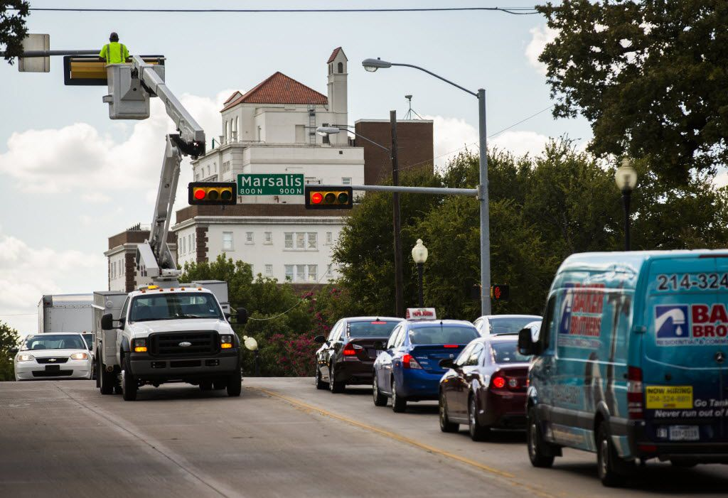 Utility workers repair a traffic signal at the corner of N Marsalis Avenue and E Colorado Boulevard on Wednesday, September 2, 2015 in the Lake Cliff area of Dallas.  (Ashley Landis/The Dallas Morning News)
