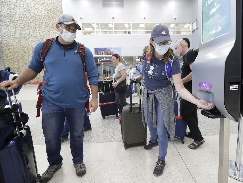 Linda Scruggs applied hand sanitizer after she and Mike Rustici arrived at Miami International Airport on March 21 on a flight from Lima, Peru.