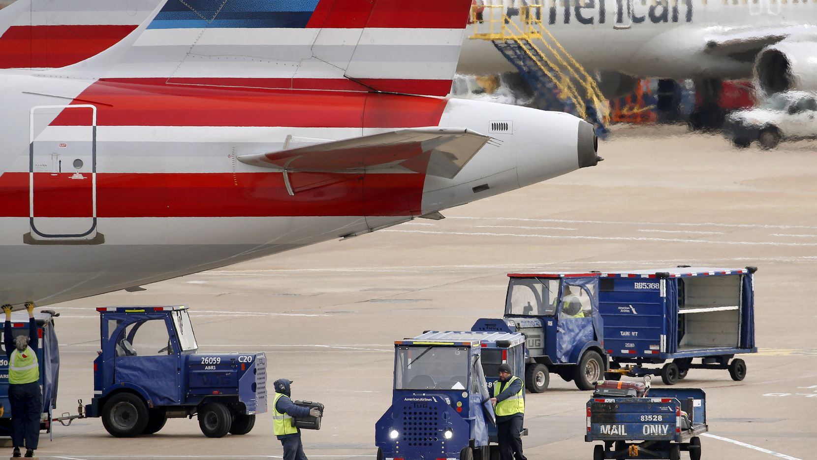 American Airlines crew members move luggage from an aircraft onto carts at Dallas-Fort Worth International Airport's Terminal C, Tuesday, January 21, 2020. (Tom Fox/The Dallas Morning News)