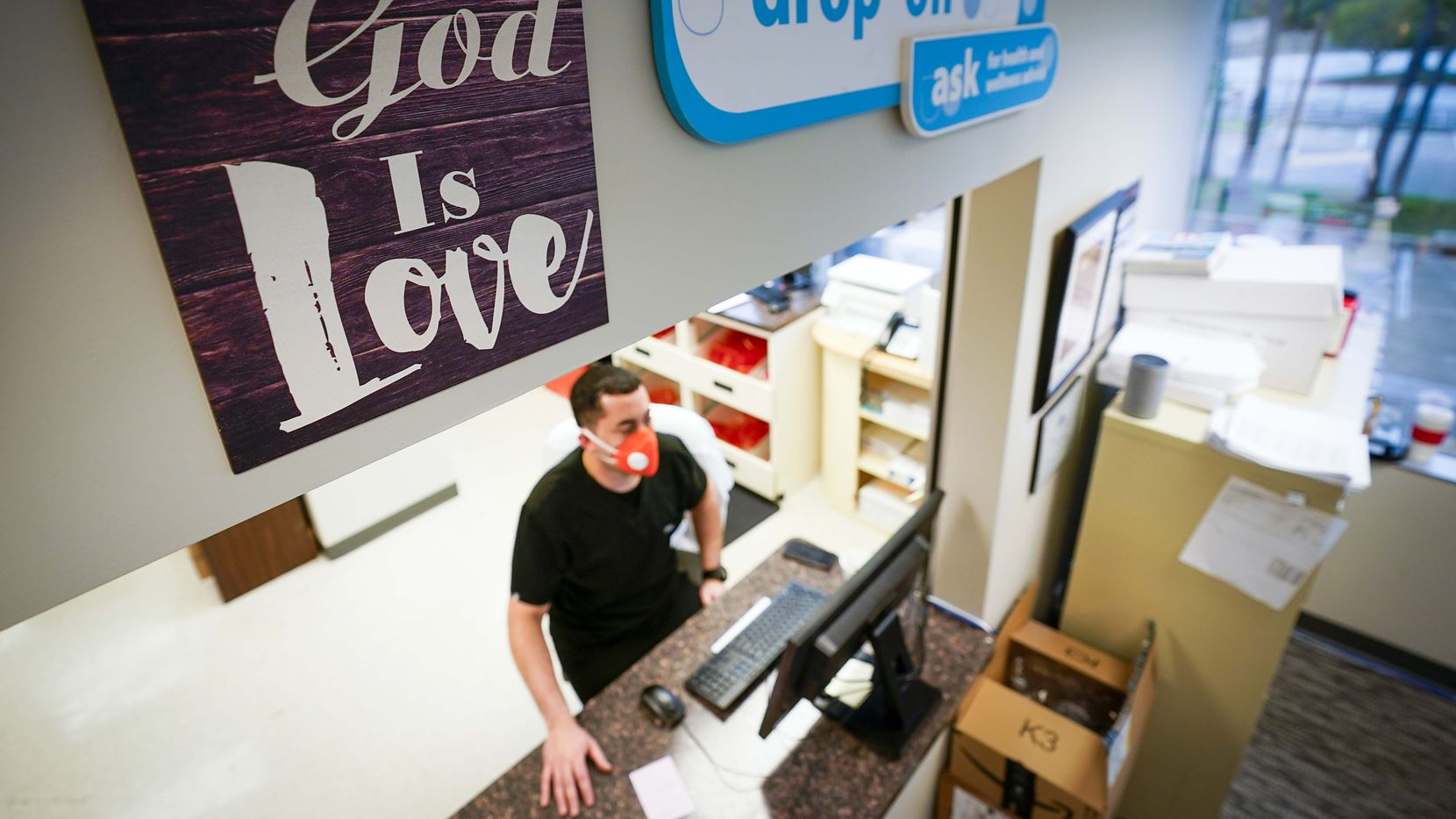 "A sign above the window reads ""God is Love"" as pharmacist Carlos Irula works at a computer at St. Vincent de Paul Pharmacy at the Northwest Community Center on Friday, April 3, 2020, in Dallas. The pharmacy doubled its prescription volume last week as the coronavirus spread in Dallas County."