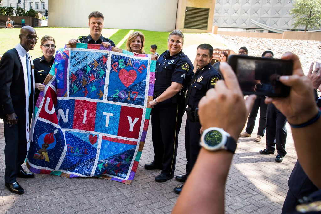 """Dallas police officers, including Chief David Pughes (right) pose for a photo with clergy and a quilt reading """"Unity"""" during a day of remembrance for last year's police ambush organized by Faith Forward Dallas at Thanks-Giving Square."""