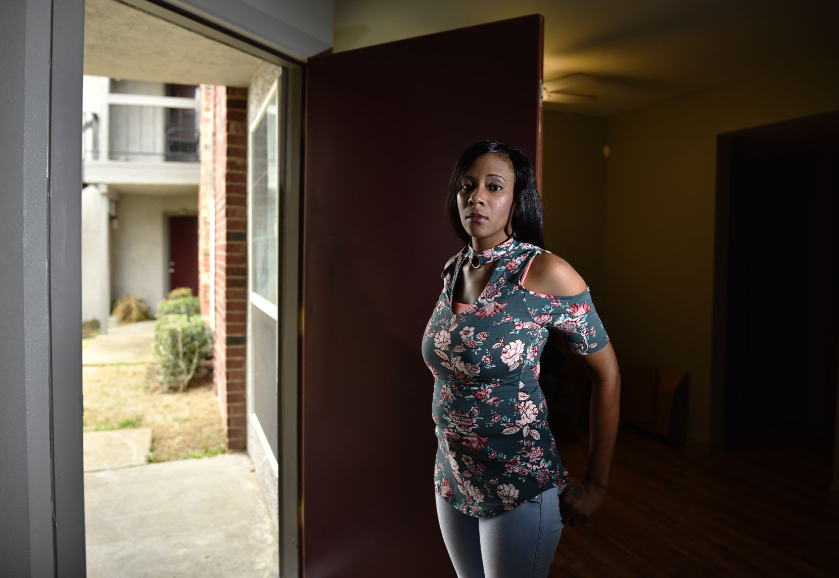 Shakena Walston, 29, originally from Tulsa, Okla., stands at the doorway of her apartment in Dallas. Walston is one of the plaintiffs in a lawsuit alleging the Dallas County jail's cash bail system unfairly harms poor people. She was jailed on accusations of assault for her involvement in a domestic dispute. Her bail was set at $15,000.