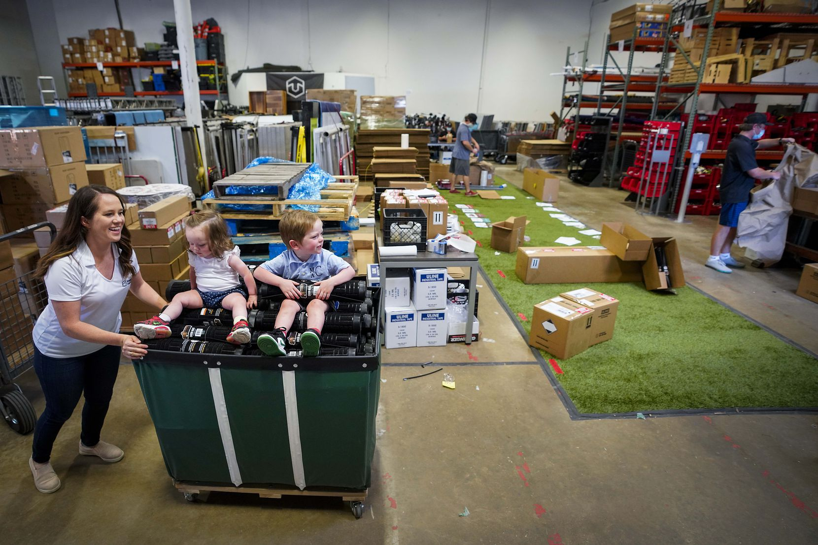 Stand Up Stations cofounder Kelsey Carroll entertains her 1-year-old daughter Ava and 2-year-old son Max as employees package hand sanitizing stations for shipping at the company's warehouse in Irving.