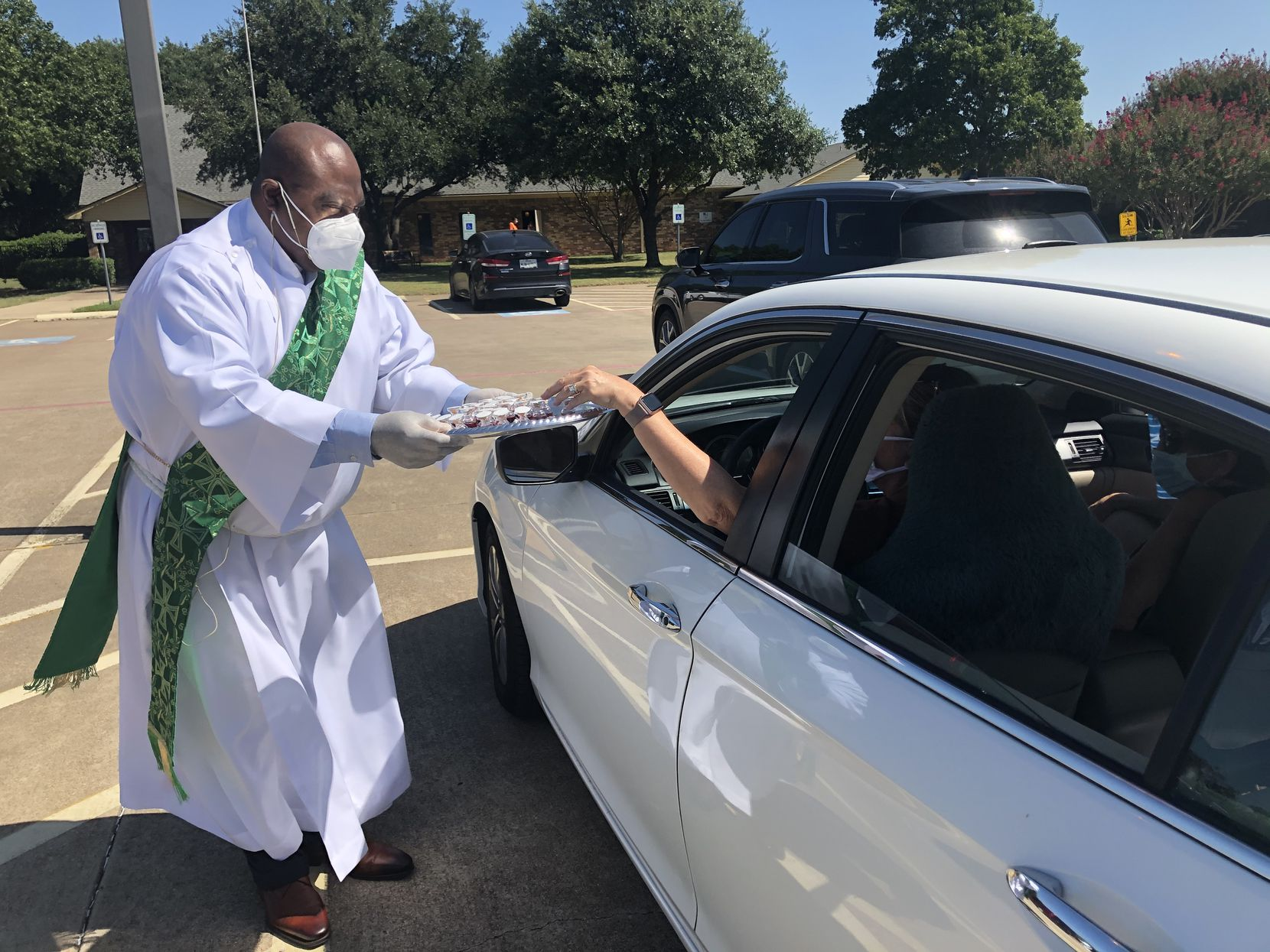 The Rev. Ayo Omoniyi goes from car to car in the St. Martin-in-the-Fields Church in Southlake during Communion on Aug. 9, 2020