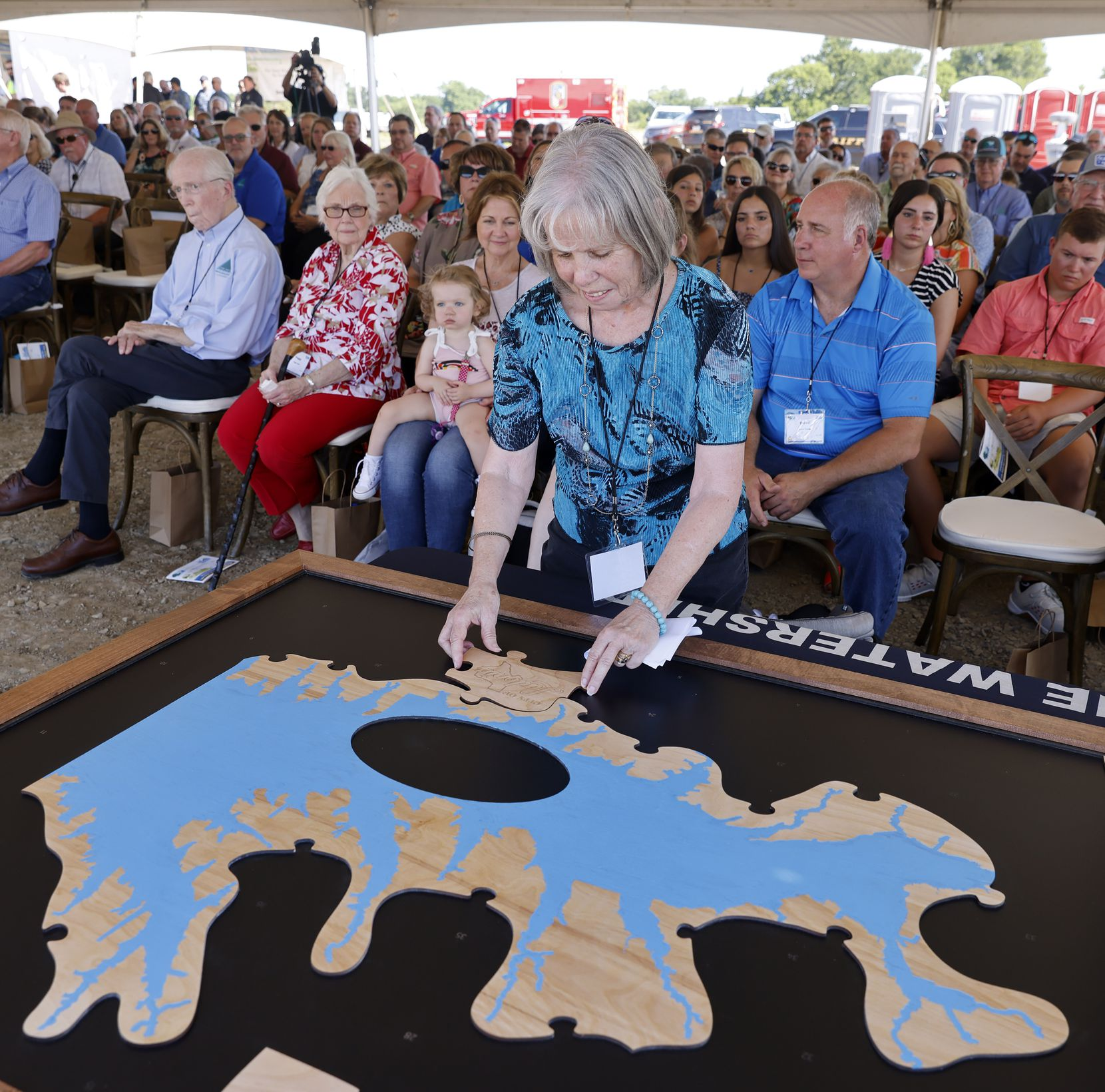 Ladonia Mayor Jan Cooper adds a wooden piece representing her city to the Upper Trinity Regional Water District puzzle. All of the organizations involved in the Lake Ralph Hall and the Leon Hurse Dam project near Ladonia were given a puzzle piece on Wednesday, June 16, 2021. The lake will provide 54 million gallons of water per day for some 29 communities in Denton and Collin counties. The $490 million project should begin delivering water by 2025. The lake is named after a U.S. representative for Texas' 4th congressional district.